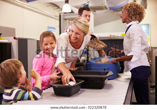 Family At Airport Passing Through Security Check