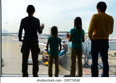 Family in airport, travel concept, silhouettes of parents with kids in terminal waiting for flight and looking at airplanes