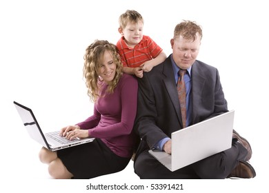 A family all looking at the computer held by the dad