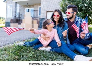 family with american flags and sunglasses sitting in garden of new house