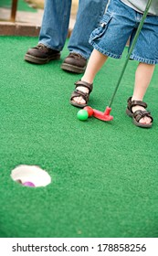 Family: Anonymous Kid Playing Mini-Golf with Dad