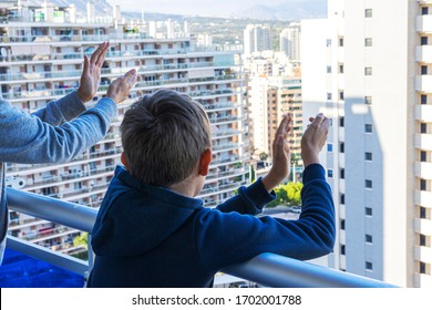 Family applauding medical staff from balcony. People clapping on balconies and windows in support of health workers during the Coronavirus pandemic