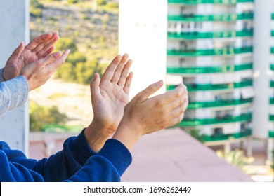 Family applauding medical staff from their balcony. People in Spain clapping on balconies and windows in support of health workers during the Coronavirus pandemic