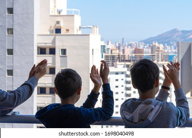 Family applauding medical staff from their balcony. People in Spain clapping gratitude on balconies and windows in support of health workers, doctors and nurses during the Coronavirus pandemic