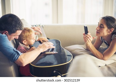 Family around guitar, young child is trying to play it, mom is taking photo
