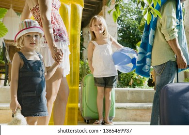 Family arriving at holiday villa with car and luggage, smiling on summer vacation outdoors. Parents and children enjoying trip together with beach lillo and inflatables, leisure recreation lifestyle.