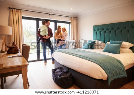 Family Arriving In Hotel Room On Vacation