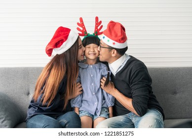 Family Asian mother and father with daughter happy and kiss together in livingroom at home in christmas day.