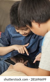 family, Asian Thai relatives brother and sister sit on a sofa together playing game on ipad