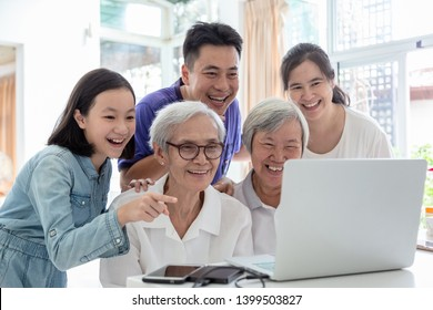 Family asian,elderly people,watching something interesting with grandmother,happy smiling senior woman and family group using laptop computer at home,technology,family,generation and people concept