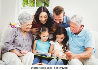 Family assisting girls while reading book at home