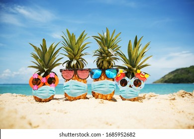 Family of attractive pineapples wearing face mask because of Air pollution or virus epidemic in the world. On the sand against turquoise sea. Summer vacation concept during an epidemic. New reality