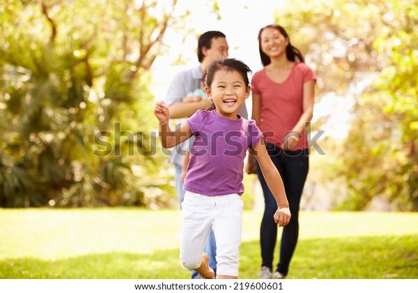 公園を歩く運送業者の赤ちゃんと家族