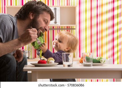 family baby daughter and dad play eat meal in toy kitchen