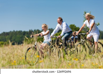 Family with baby and and daughter having a weekend excursion on their bikes on a summer day in beautiful landscape