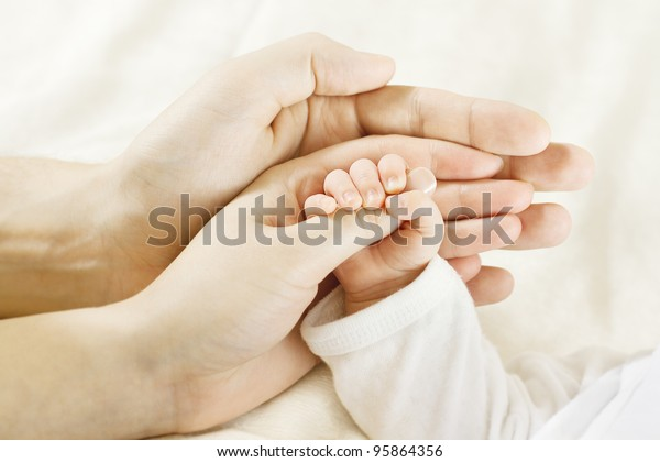 Family Baby Hands. Father and Mother Holding Newborn Kid. Child Hand Closeup into Parents
