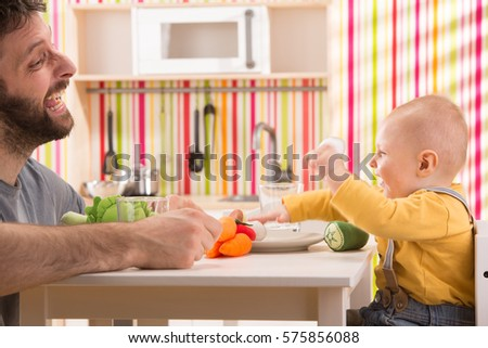 Family Baby Son And Dad Play Eat Meal In Toy Kitchen