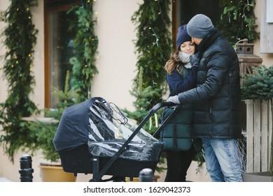 Family with a baby stroller walk in the city
