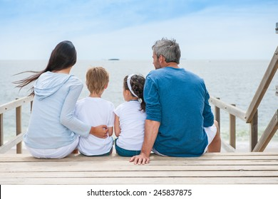 family back sitting on a wood pontoon at seaside watching the horizon
