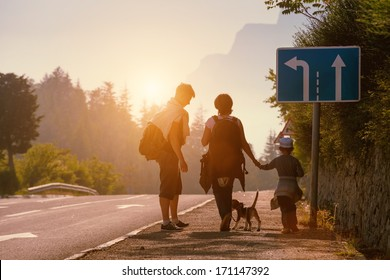 Family backpackers goes on mountain road at sunset