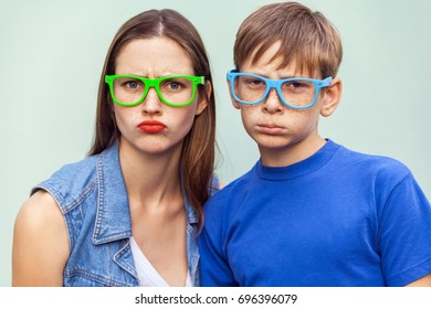 Family, bad emotions and feelings. Older sister and her brother with freckles, posing over light blue background together, looking at camera with unhappy faces. Studio shot