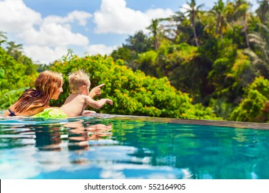 Family Bali beach holiday concept. Happy son with mother - active baby at poolside in infinity swimming pool. Summer healthy lifestyle and children water activity, games and lessons with parents.
