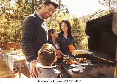Family barbecuing on a deck in the forest