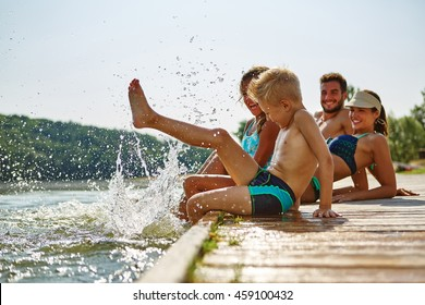 Family bathing and splashing water with their foot at a lake in summer