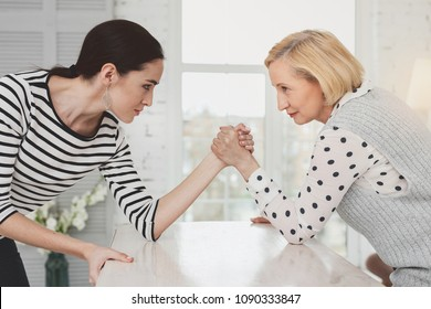 Family battle. Nice young woman looking at her mother in law while having a competition with her