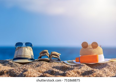 Family beach accessories. Father's sunhat, mother's bonnet hat, sandals of a child and bottle of sunscreen against the sea.