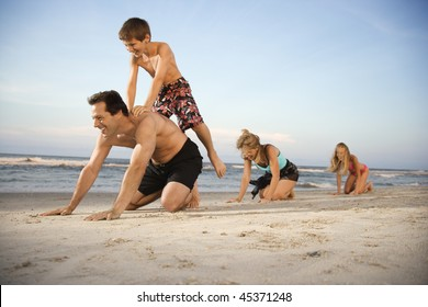 Family at the beach playing leap frog. Horizontal shot.