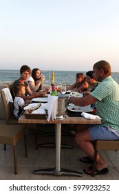 Family in the beach restaurant at sunset