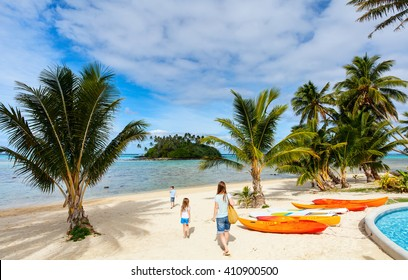 Family  at beautiful tropical beach with palm trees, white sand, turquoise ocean water and blue sky at Cook Islands, South Pacific