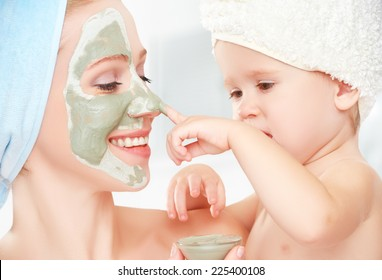 family beauty treatment in the bathroom. mother and daughter baby girl make a mask for a face skin