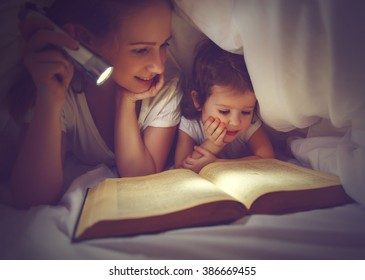 Family bedtime. Mom and child daughter reading a book with a flashlight under the blanket in bed