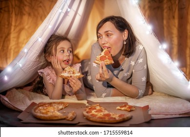 Family bedtime. Mom and daughter eat pizza in a tent. Pretty young mother and lovely girl having fun in children room.