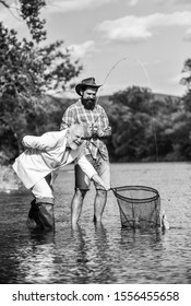Family is Best. retired dad and mature bearded son. Catching and fishing concept. happy fishermen. Good profit. Two male friends fishing together. fly fish hobby of businessman. retirement fishery.