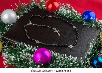 A family Bible with Christmas decorations and silver rosary