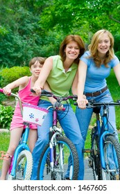 Family Bicycling Fun – A mother and two daughters clown around on their bicycles for some summer fun.