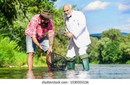 Family bonding time. fly fish hobby of businessman. retirement fishery. retired dad and mature bearded son. Two male friends fishing together. happy fishermen friendship. Catching and fishing concept.