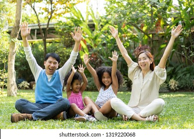 Family bonds. Happy multiethnic family smiling while spending free time outdoors. parents or Volunteers take care of orphans pretty little daughter in child care center concept