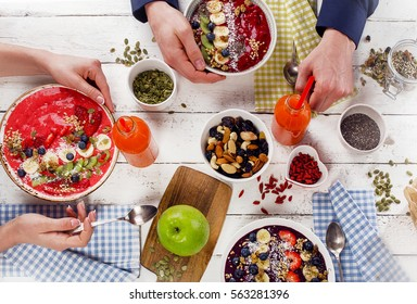 Family Breakfast with berries smoothies and superfood on a white wooden table. Healthy eating concept. Top view