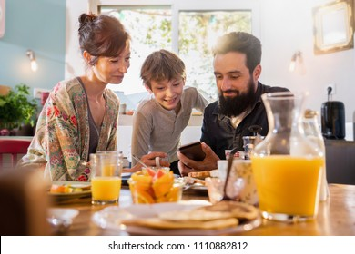 Family breakfast, Dad shares a video on a phone to his son. Mom looks over her son's shoulder as the morning sun enters through the window