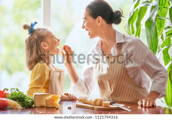 Family breakfast. Mother and her child daughter cutting bread and cheese in morning.