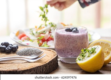 Family breakfast table with chia blueberries smoothie and fresh salad. Toddler boy hand picking on lettuce at the background of the photo