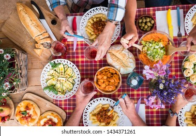 Family brunch at sunday. Four people enjoying togetherness and friendship with healthy eating. Mix of vegetables and italian pasta