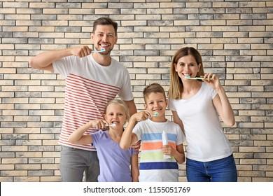 Family brushing teeth against brick wall