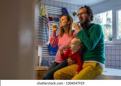 Family brushing teeth together on authentic bathroom.