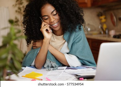 Family budget and finances. Cute African woman with Afro haircut and braces having phone conversation and smiling while doing paperwork, calculating domestic expenses, paying bills online on laptop