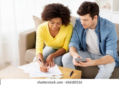family budget, finances and people concept - couple with papers and calculator counting money at home